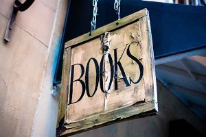 """image of sign hanging from two chains reading """"Books"""""""
