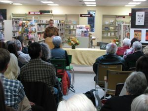 "photo of guests at book launch at the Carberry Library with Marnie Sluman Somers reading from the book ""The Amulet"""