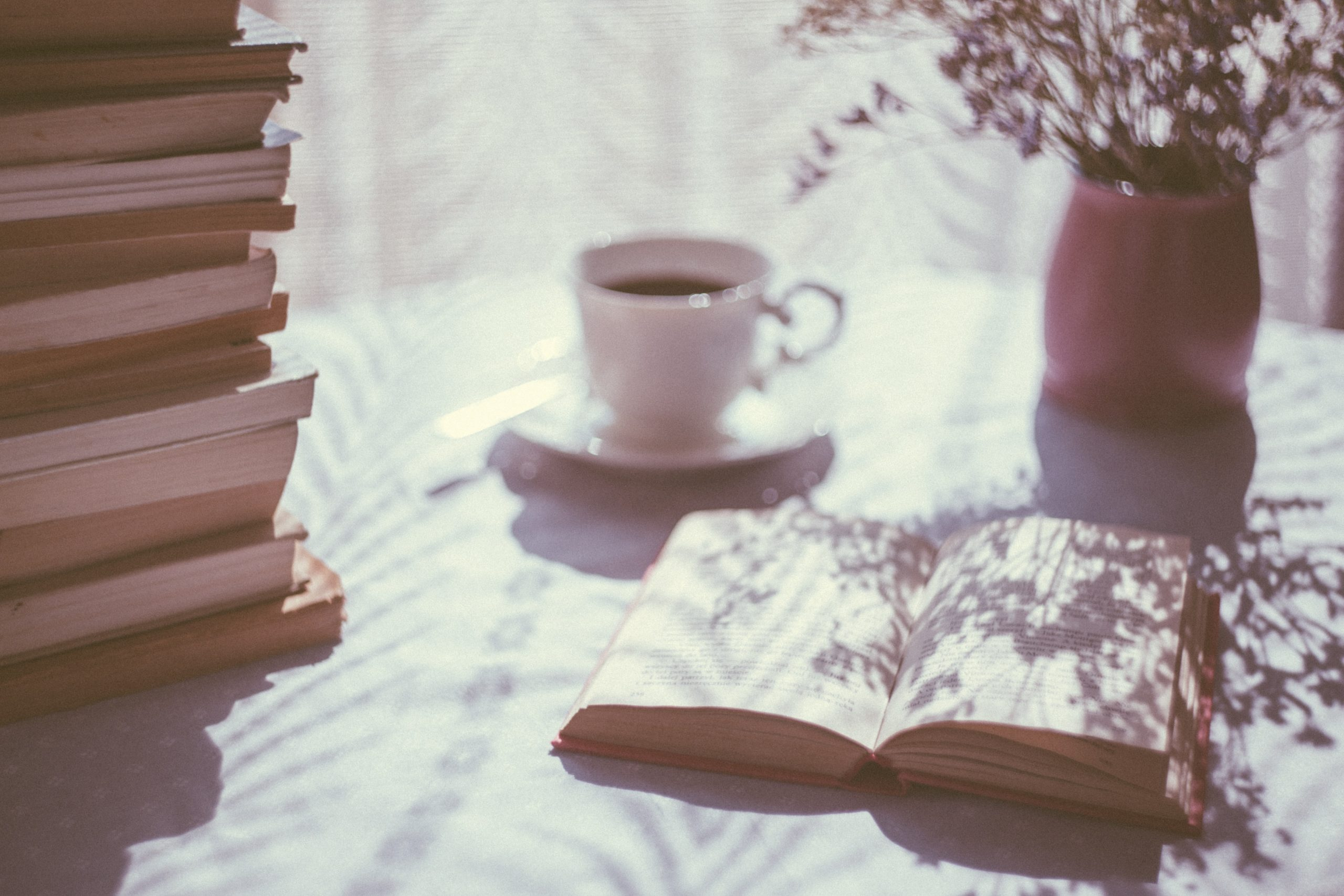 image of an open book and cup on a table