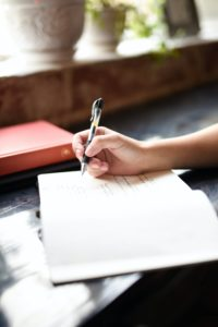 a hand holding a pen above a blank page, why do you write?