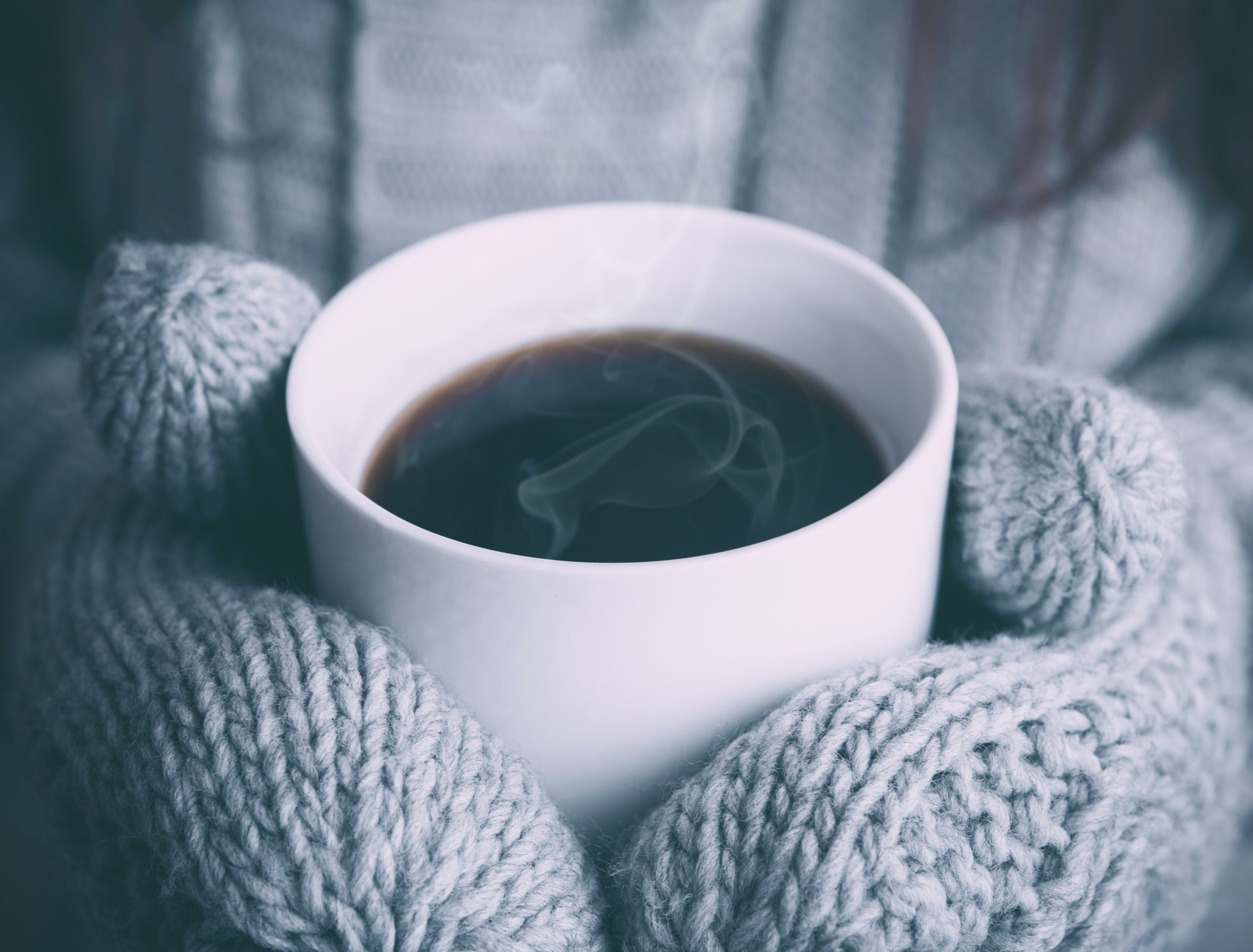 mittened hands hold a mug of coffee