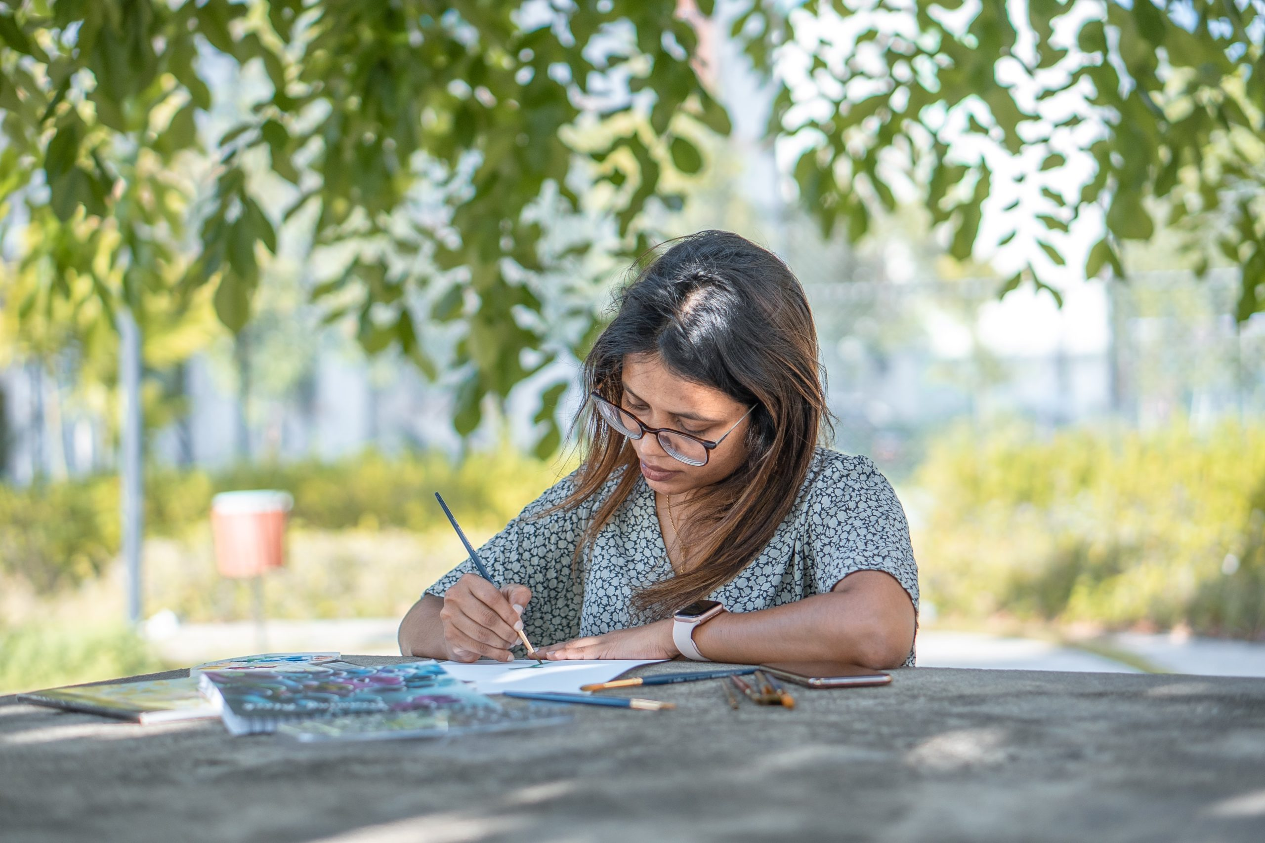 A woman with dark hair and glasses looks closely at the open book in front of her, pen poised to write. She is sitting outside and is surrounded by green leaves.