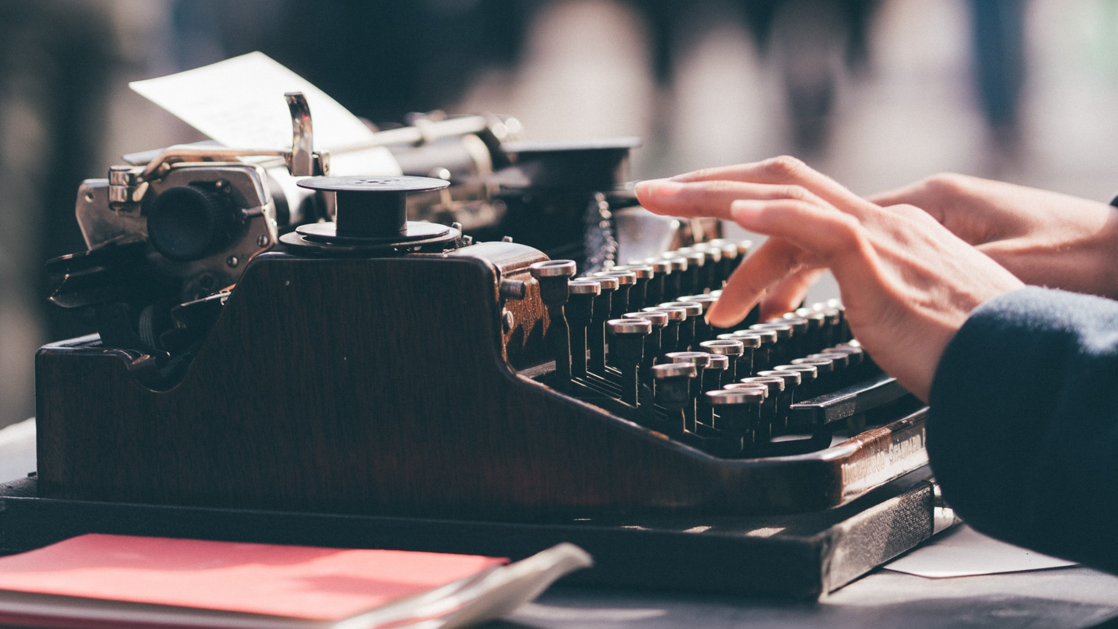 fingers poised to write over the keyboard of a black typewriter