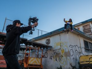 a dark man holds up a movie camera to film an actor sitting on the edge of a graffiti covered building